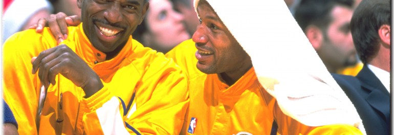"AC and teammate Ron Harper watch the game with ""Little AC"""